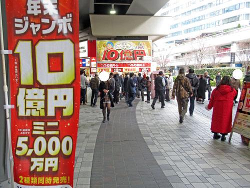 年末ジャンボ宝くじ10憶円ののぼりの奥には派手な看板の大黒天売場