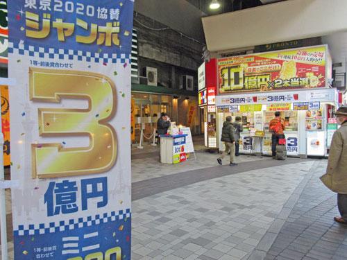 東京2020ジャンボ宝くじののぼりの奥には多くのお客さんで混雑している大黒天売場
