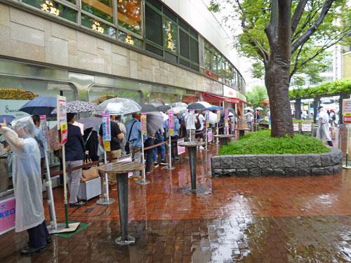 雨の中傘を差しながら頑張って並んでいる1番窓口の行列のお客さん