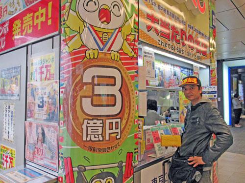 東京2020ジャンボ宝くじ3憶円の派手な看板の窓口でジャンボ宝くじを購入中の私