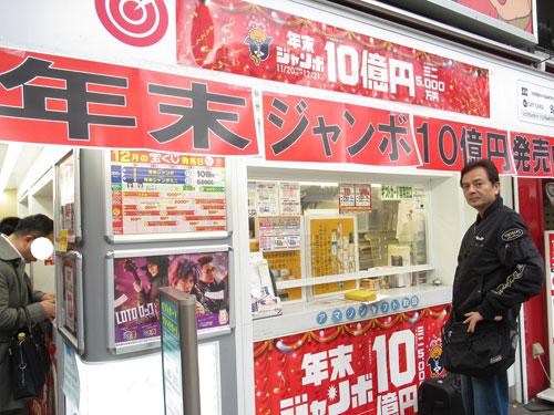 年末ジャンボ10億円の看板の窓口で宝くじを買う私