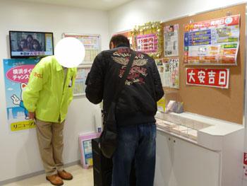 売場の端っこで担当者から宝くじを購入中