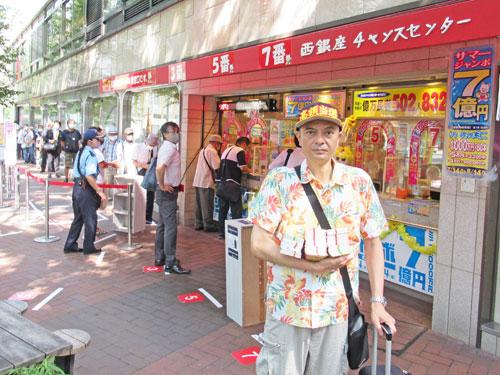 今日買ったサマージャンボ宝くじを抱えて売場の前で記念撮影