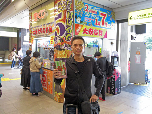 売場の前で今日買ったハロウィンジャンボ宝くじを持って記念撮影