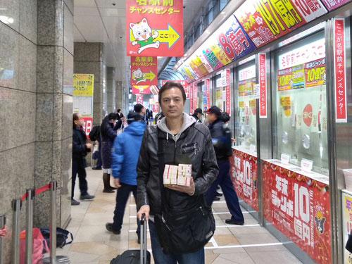 名駅前チャンスセンターの売場の前で年末ジャンボ宝くじを持って記念撮影
