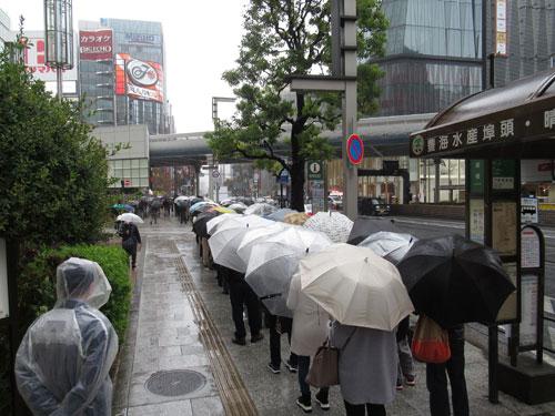 雨が降るなかでの1番窓口の行列最後尾の看板