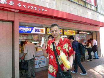 売場の前で買った宝くじを持ってワンショット