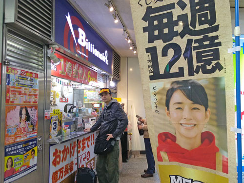 MEGABIG12憶円毎週と書かれたのぼりの奥には宝くじを購入中の私