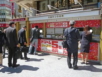 お昼時で多くのお客さんで大混雑している宝くじ売場