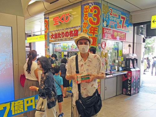 池袋駅東口西武線構内売場の前で今日買ったサマージャンボ宝くじを持って記念撮影
