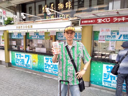 売場の前で今日買ったサマージャンボ宝くじを持って記念撮影
