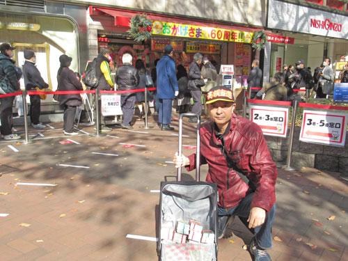 売場の前で今日買った年末ジャンボ宝くじをバックに詰めて記念撮影