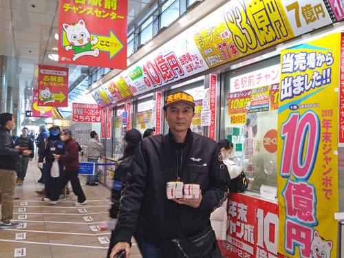 名駅前チャンスセンターの前で今日買った年末ジャンボ宝くじを持って記念撮影