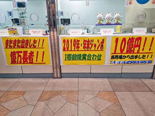 名駅前チャンスセンターの窓口の下には年末ジャンボ宝くじ1等10憶円当選の看板