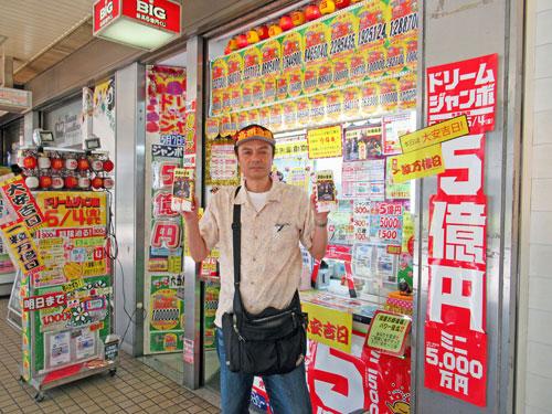 大阪駅前第2ビルラッキーセンターの前で今日買った宝くじを持って記念撮影