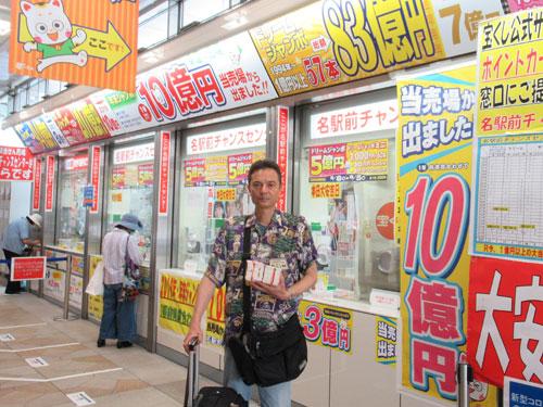 売場の前で今日買ったドリームジャンボ宝くじを持って記念撮影