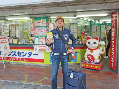 新宿チャンスセンターの前で今日買った宝くじを持って記念撮影