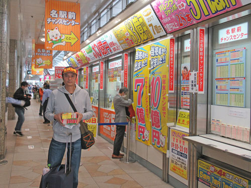 名駅前チャンスセンターの前で今日買った宝くじを持って記念撮影