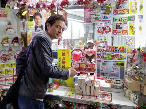窓口で高橋さんから年末ジャンボ宝くじを買っているところ