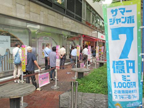 サマージャンボ宝くじ7億円ののぼりの奥には1番窓口の多くのお客さんの行列