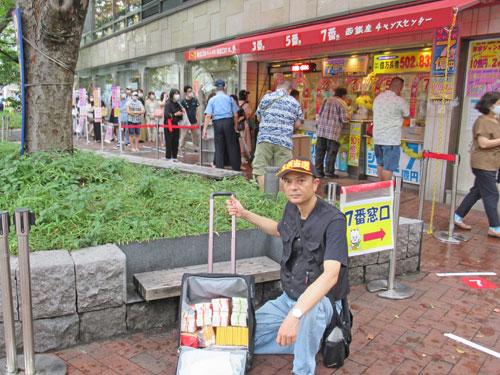 売場の前で今日買ったサマージャンボ宝くじをバックに入れて記念撮影