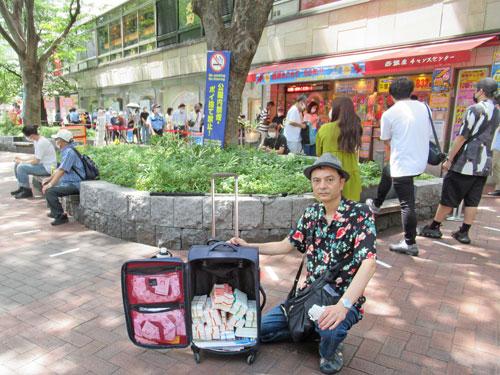 新宿チャンスセンターの前で今日買ったサマージャンボ宝くじをバックに詰めて記念撮影