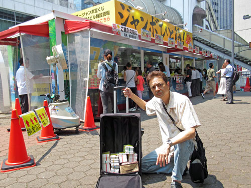 大阪駅前第4ビル特設売り場の前でサマージャンボ宝くじのポーズ