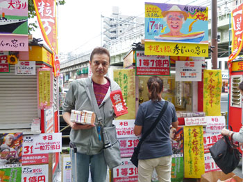 売場の前で買った宝くじを抱えて記念撮影