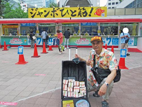 売場の前で今日買ったサマージャンボ宝くじをバックに詰めて記念撮影