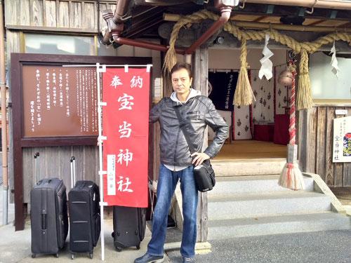 拝殿の前の宝当神社の云われの看板の前で記念撮影
