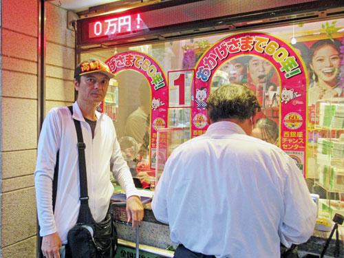 西銀座チャンスセンターの一番窓口で宝くじを購入中
