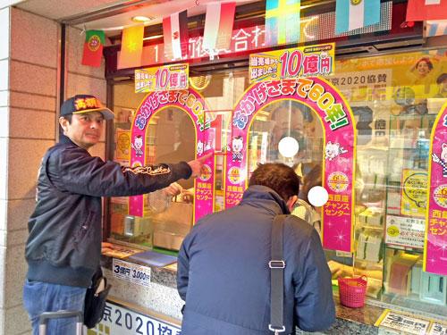 派手な装飾の1番窓口で2020年度ジャンボ宝くじを購入中の私