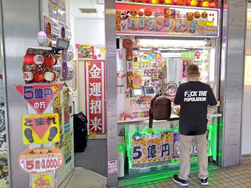 大阪駅前第2ビルラッキーセンターで宝くじを購入中のお客さん