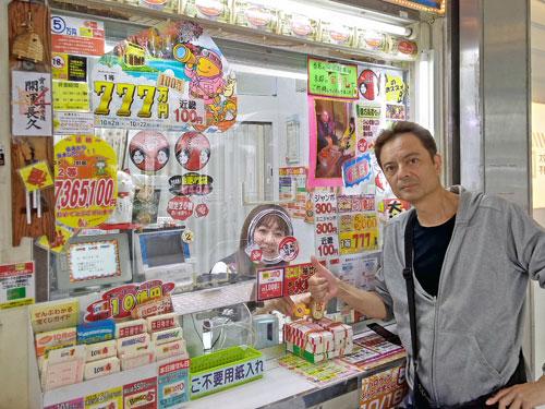 派手な装飾の宝くじ売場の前で記念撮影をする私