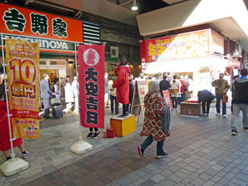 売場の前でマイクパフォーマンスの女性