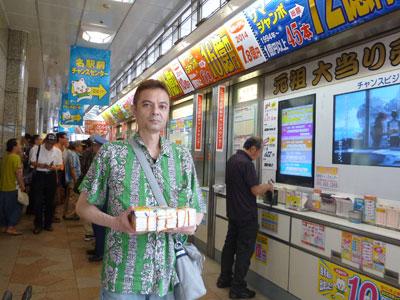 売場の前で購入したサマージャンボ宝くじを持って記念撮影