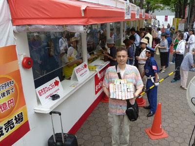 売場の前で購入したサマージャンボ宝くじを抱えて記念撮影