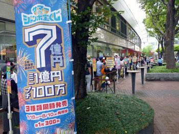 サマージャンボ7億円の看板の奥に1番窓口の長い行列